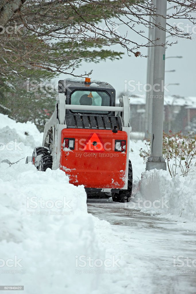 Mini Front End Loader Removing Snow From A City Sidewalk stock photo