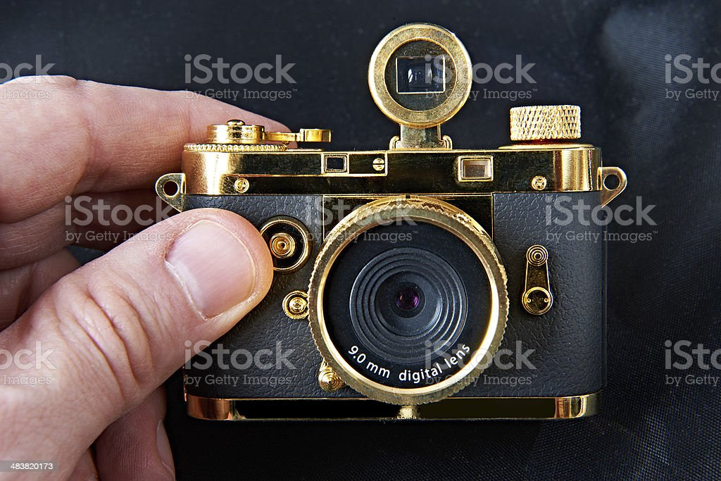 Mini gift golden camera in big hand royalty-free stock photo
