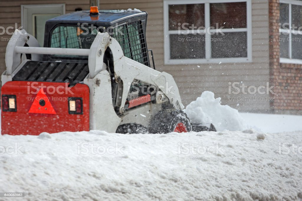 Mini Loader Clearing Snow On Residential Sidewalk stock photo