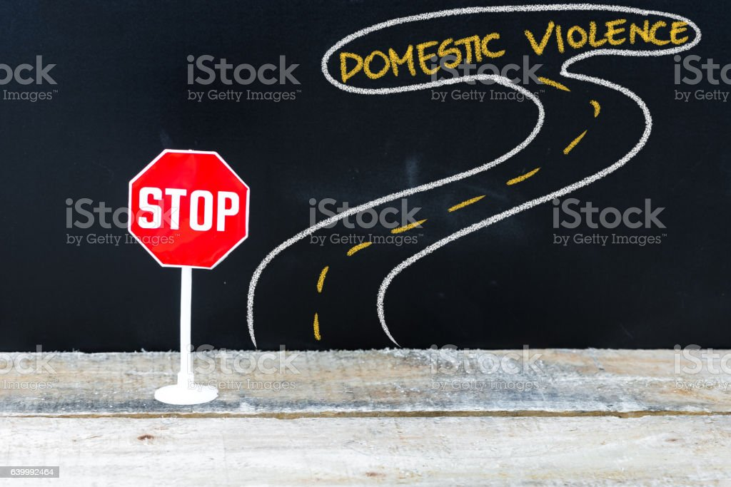 Mini STOP sign on the road to DOMESTIC VIOLENCE stock photo