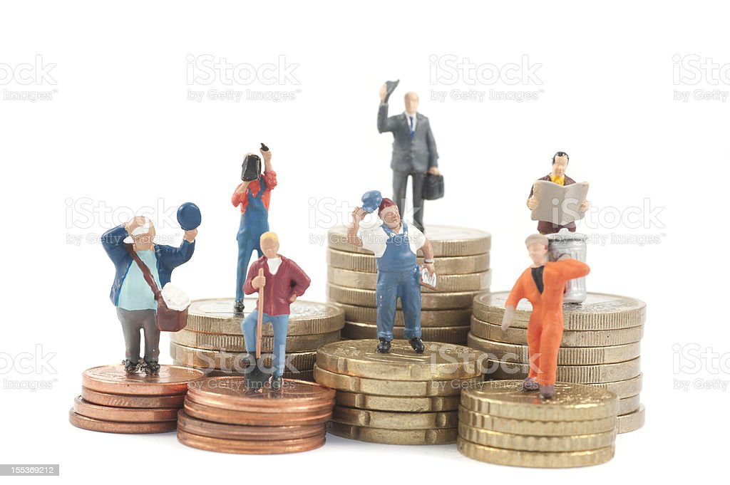 Miniature business people on stacks of coins stock photo