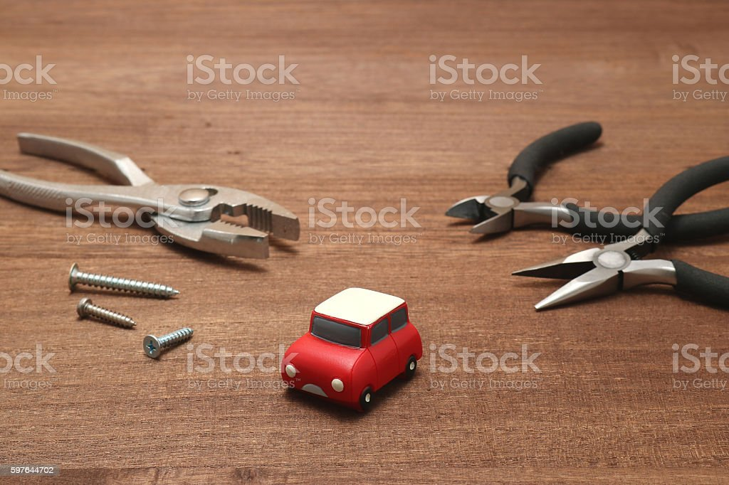 Miniature car and maintenance tools on wood. stock photo