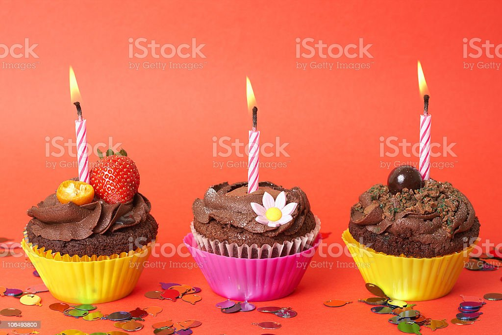 Miniature chocolate cupcakes with candles royalty-free stock photo