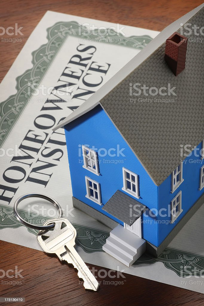 Miniature house and house key on homeowners insurance policy royalty-free stock photo