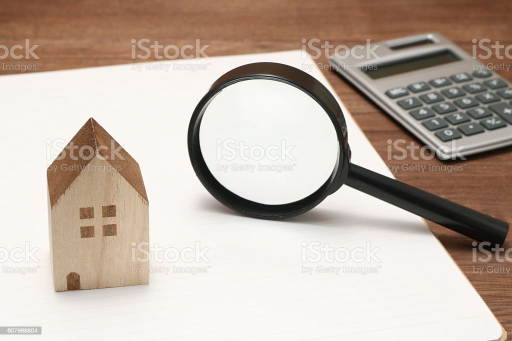 Miniature house, magnifying glass, calculator, and notebook. stock photo