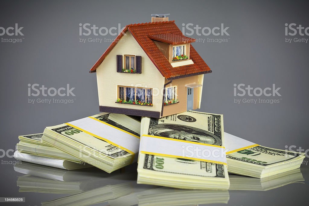 Miniature house on bundles of $100 bills stock photo