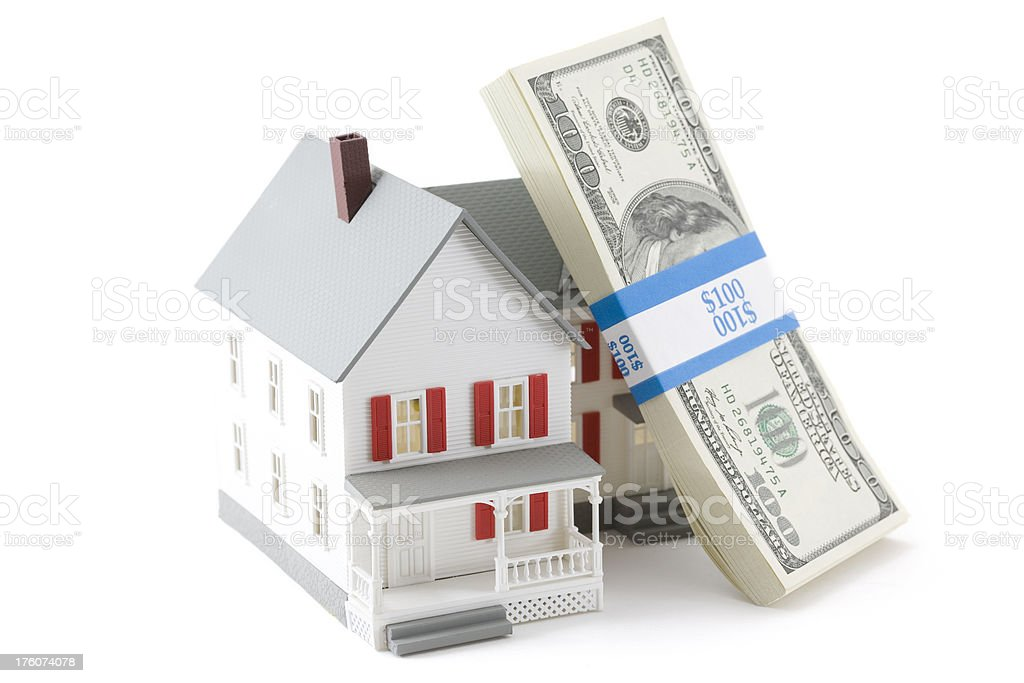 Miniature House with Stack of U.S. Bills Leaning Against it royalty-free stock photo