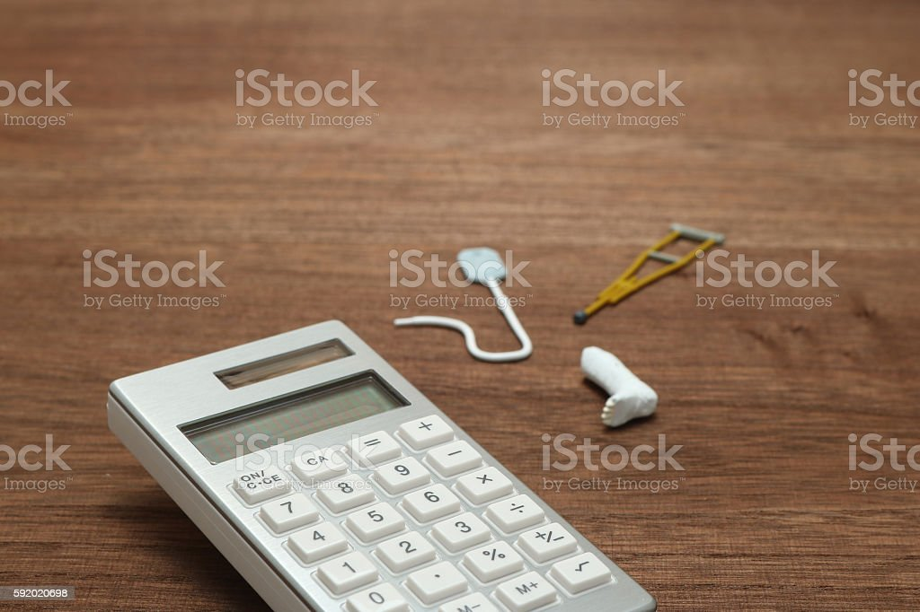 Miniature items of illness or injury beside calculator. stock photo