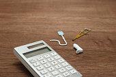 Miniature items of illness or injury beside calculator.