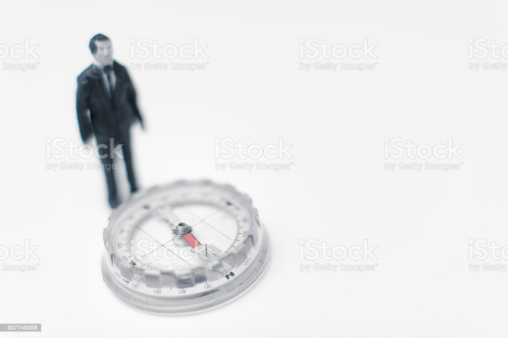 miniature man finding his way stock photo