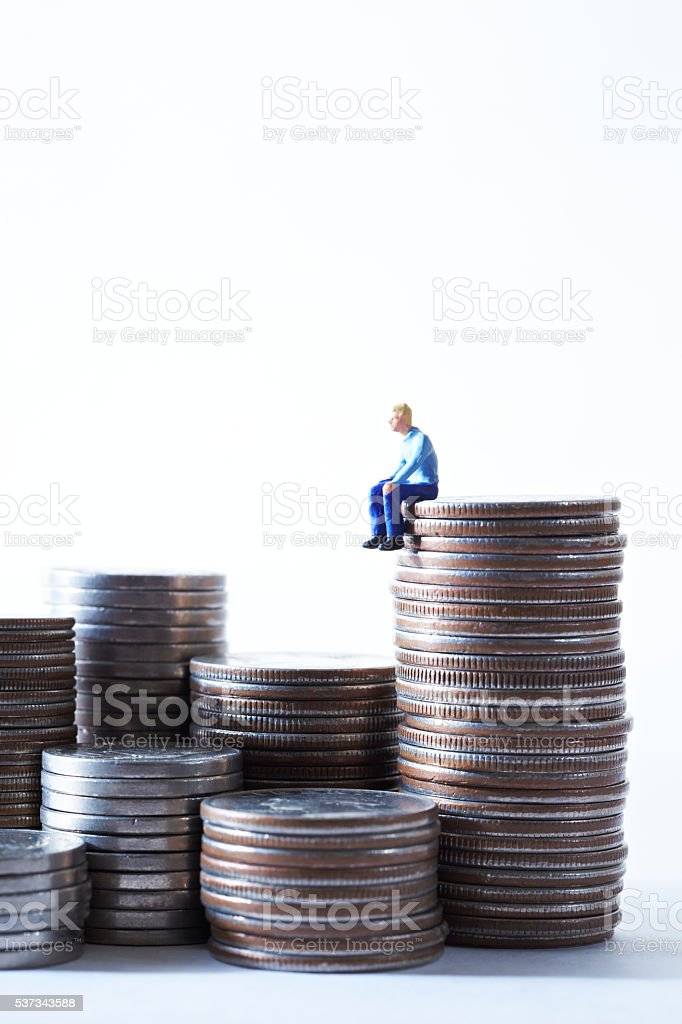 Miniature man sitting alone on pile of coins stock photo