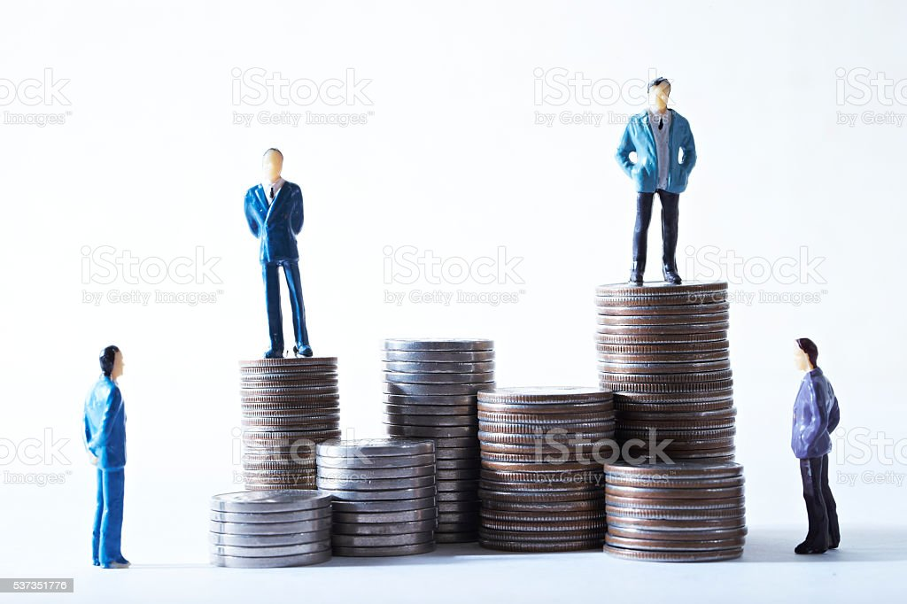 Miniature men on pile of coins stock photo