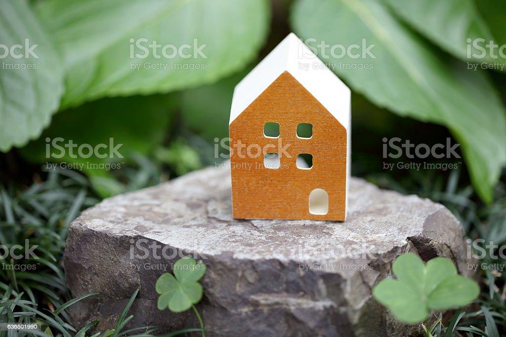 Miniature model of house on stone stock photo