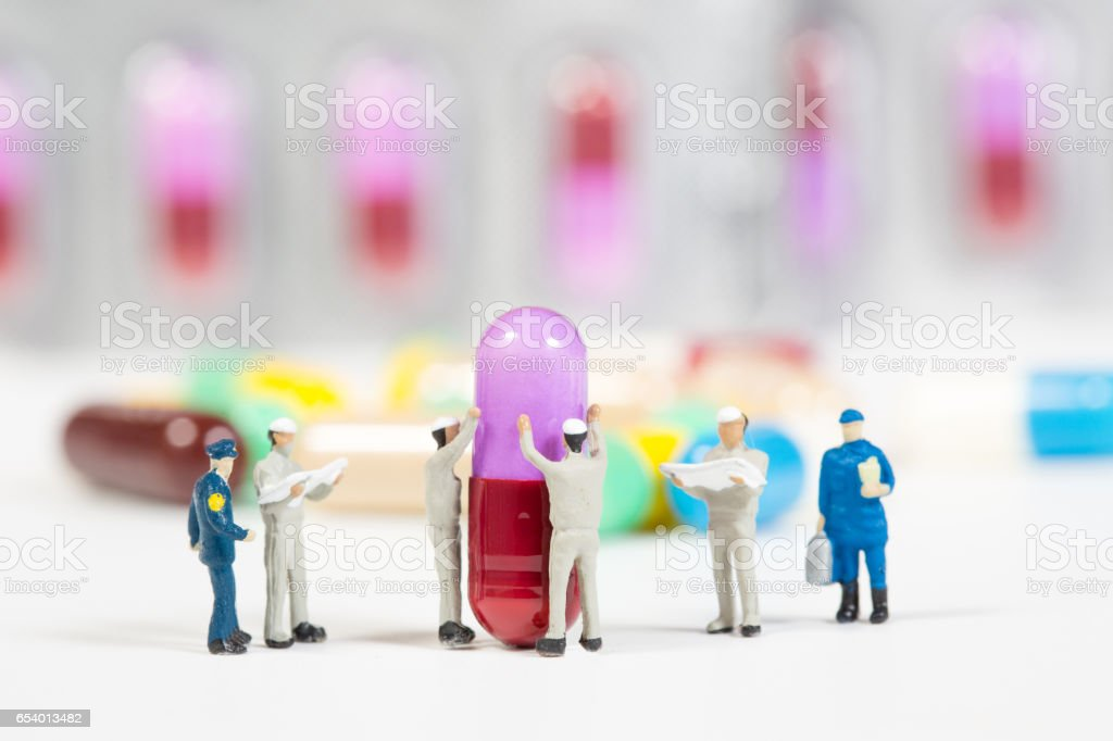 miniature people on the drugs or pils on white,medical concept stock photo