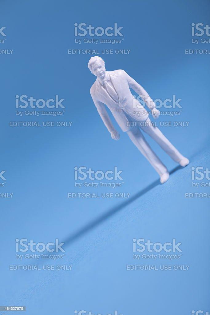 Miniature plastic figurine on blue background royalty-free stock photo