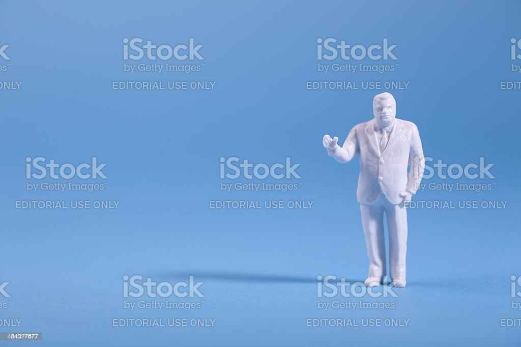 Miniature plastic figurine on blue background royalty-free stock photo