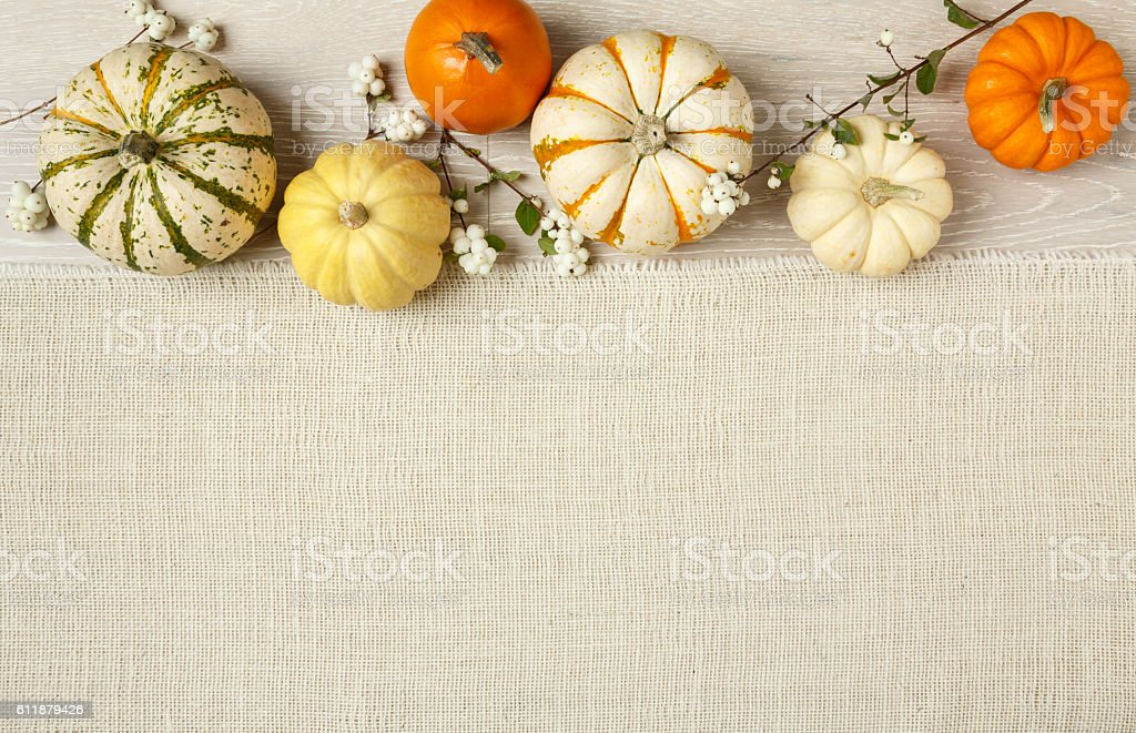 Miniature pumpkins on rustic wood and burlap cloth background stock photo
