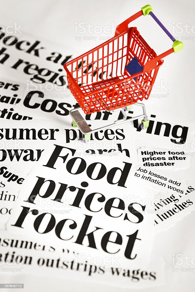 Miniature shopping cart on press headlines concerning cost of living royalty-free stock photo
