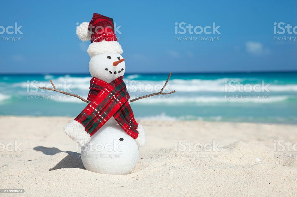 Miniature Snowman Wearing Hat and Scarf on the Beach stock photo