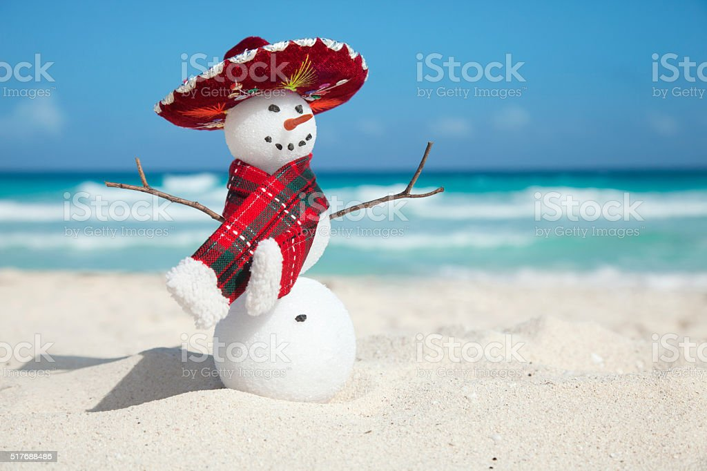 Miniature snowman wearing Mexican sombrero and scarf on the beach stock photo