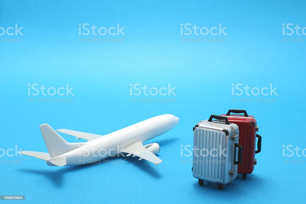 Miniature toy airplane and suitcases on blue background. stock photo