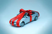Miniature toy car wrapped in red ribbon with bow