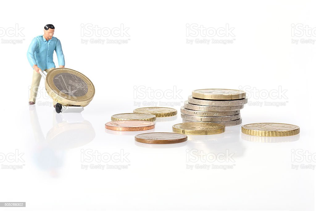 Miniature worker drives euro coins stock photo