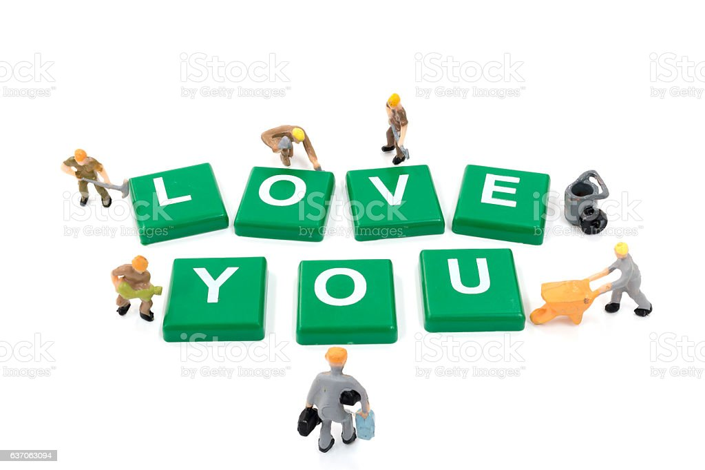 Miniature worker team building word love you on white background stock photo