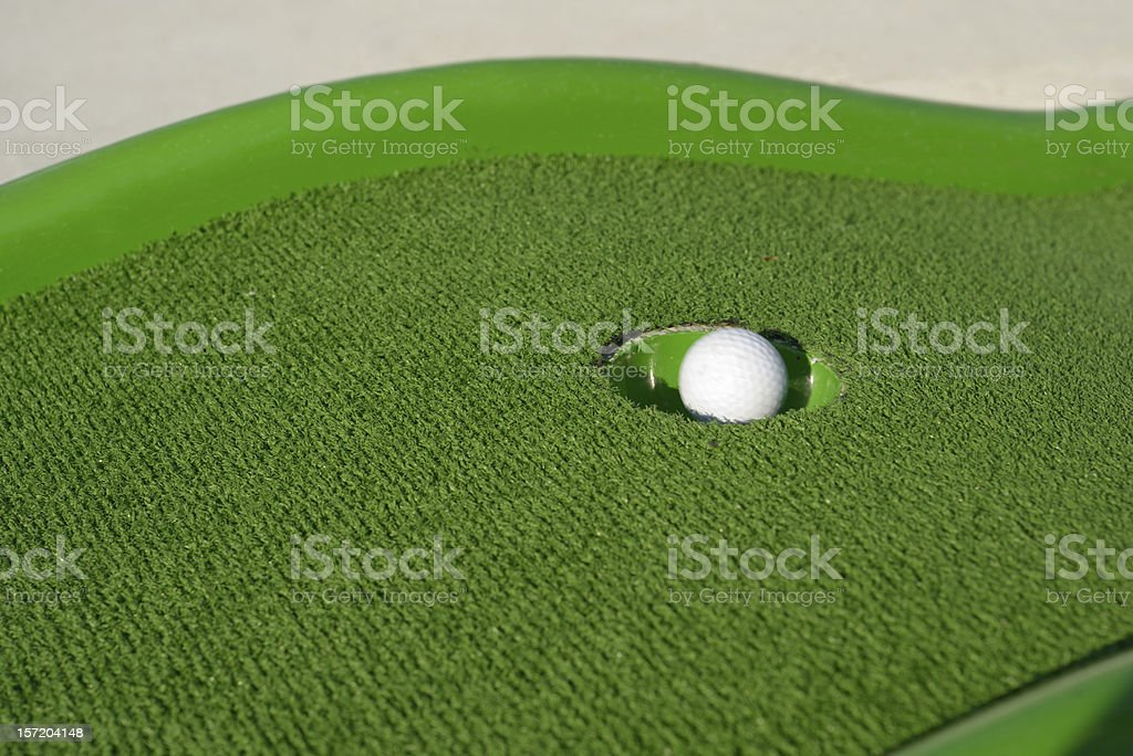 Minigolf ball in a hole royalty-free stock photo