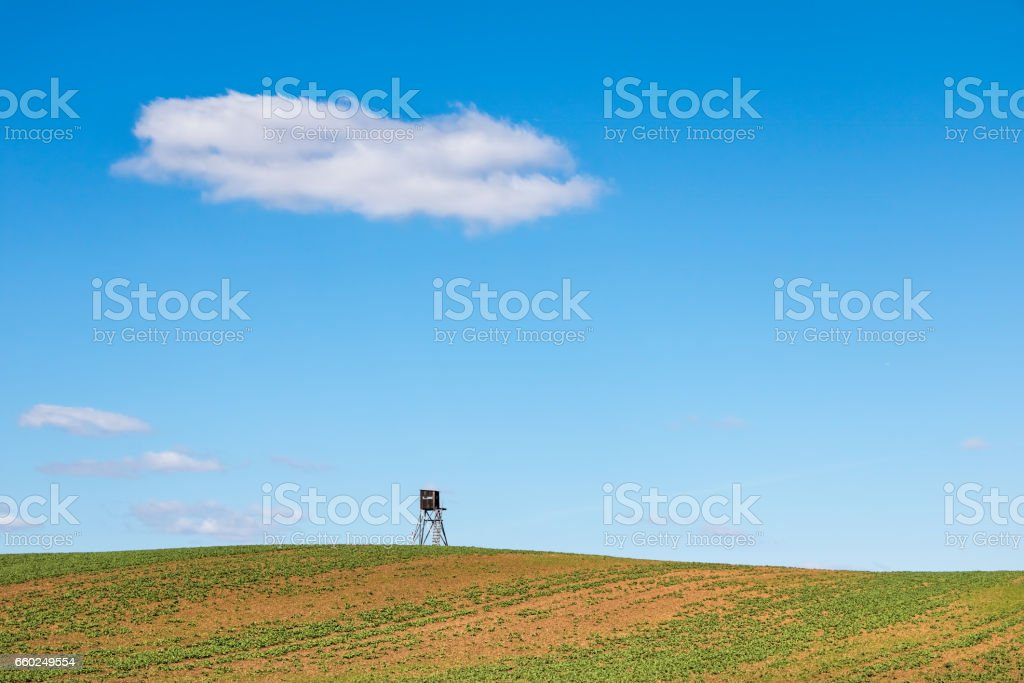 Minimalist spring landscape with field and hunting hide stock photo
