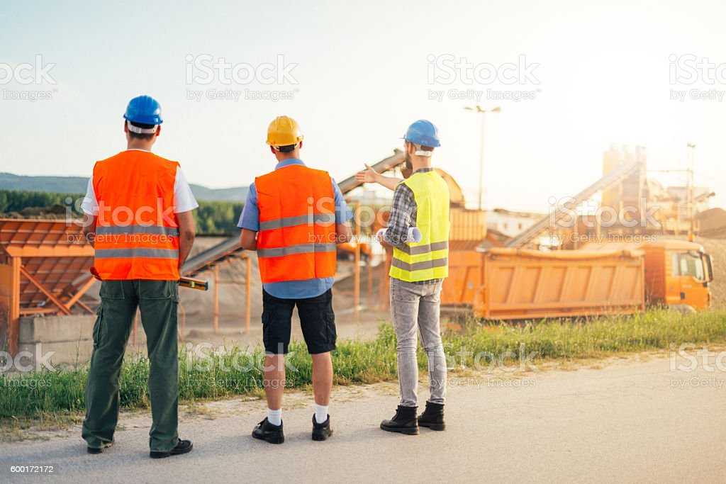 Mining pit and engineers discussing expansion possibilities stock photo