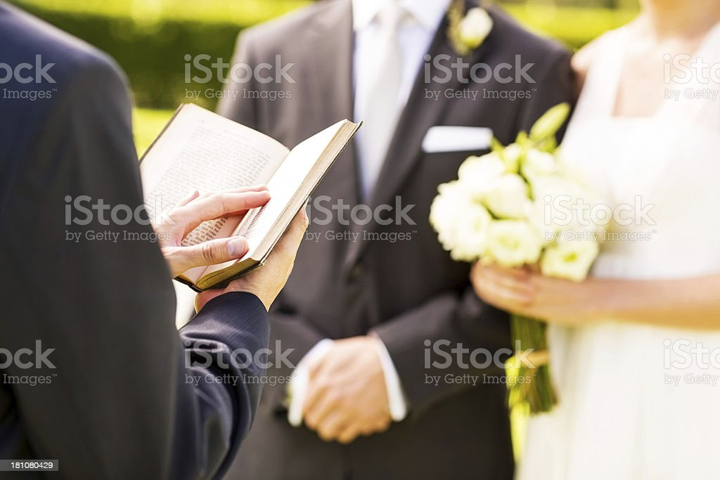Minister Holding Bible With Bride And Groom At Outdoor Wedding royalty-free stock photo