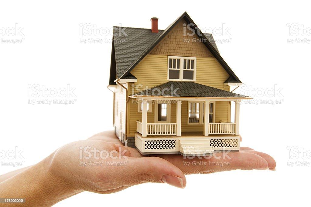 Miniture model house sitting on human hand isolated white stock photo