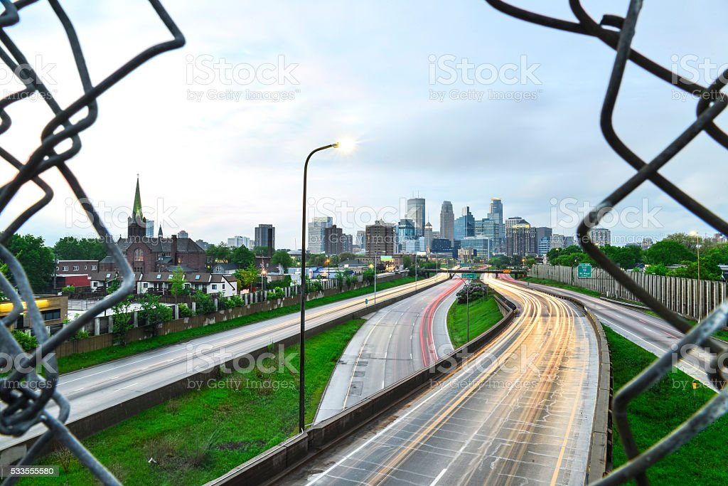 Minneapolis Skyline through the Wire or Fence and Freeway Traffic stock photo