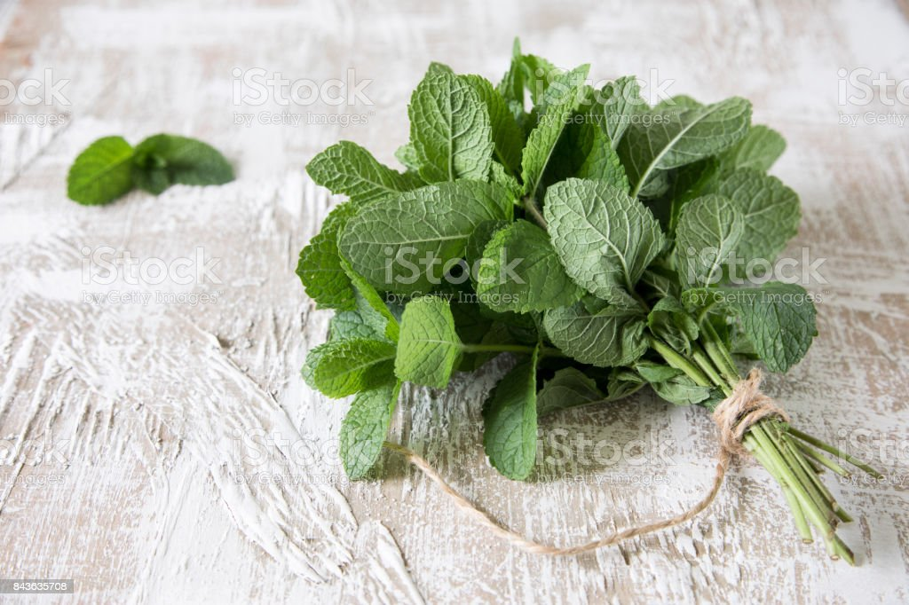 Mint. Bunch of Fresh green organic mint leaf on wooden table closeup. Selective focus. stock photo