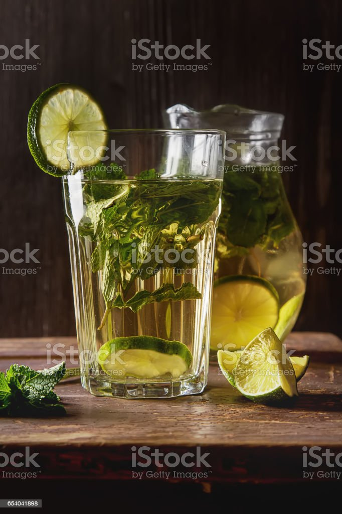 Mint iced tea with lime in the glass. Dark background. stock photo
