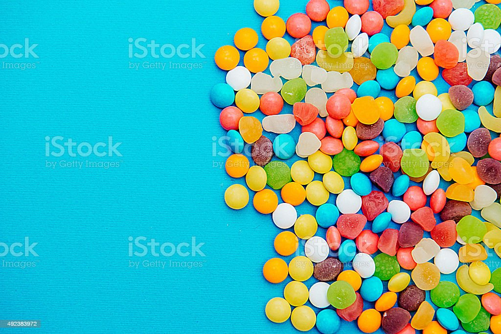 Mint, jellybeans and bonbons - sweet food concept on blue stock photo