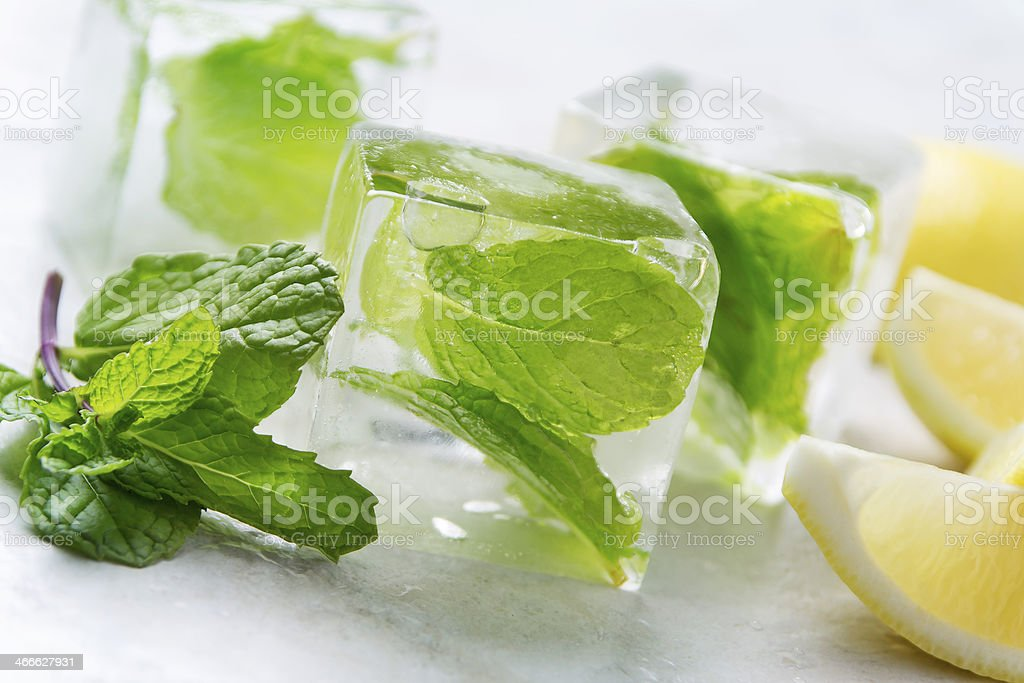 Mint leaves infused in ice cubes next to lemon slices stock photo