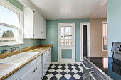 Mint walls and white and black square tiled kitchen floor