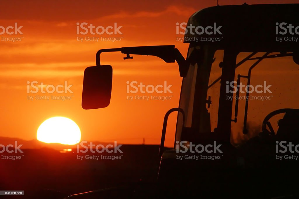 Mirror and Cab of Farm Harvester Silhouetted by Vibrant Sunset royalty-free stock photo