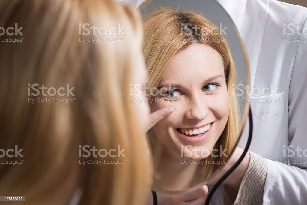 Mirror image of a smiling woman putting in her contact lens stock photo