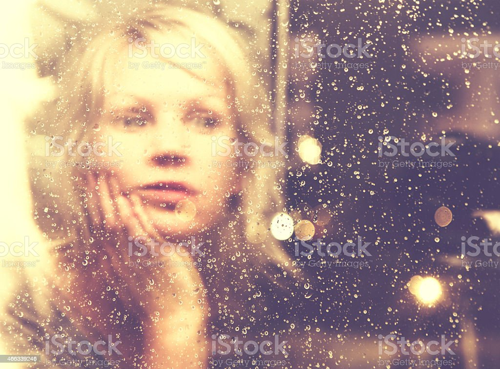 Mirror image of a woman in window with rain drops stock photo