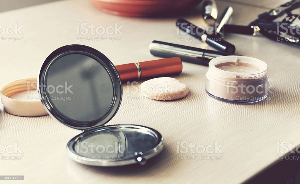 Mirror, powder, puff, eyeliner and other cosmetics on the table royalty-free stock photo