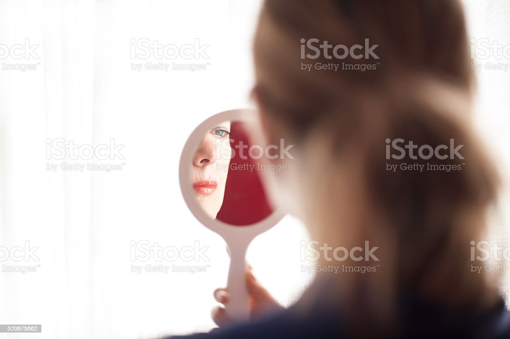 Mirror reflection of mature woman stock photo