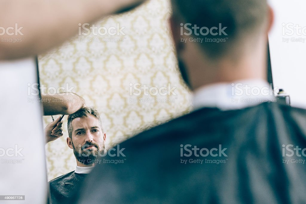 mirror view of bearded man hair cut in barber shop stock photo