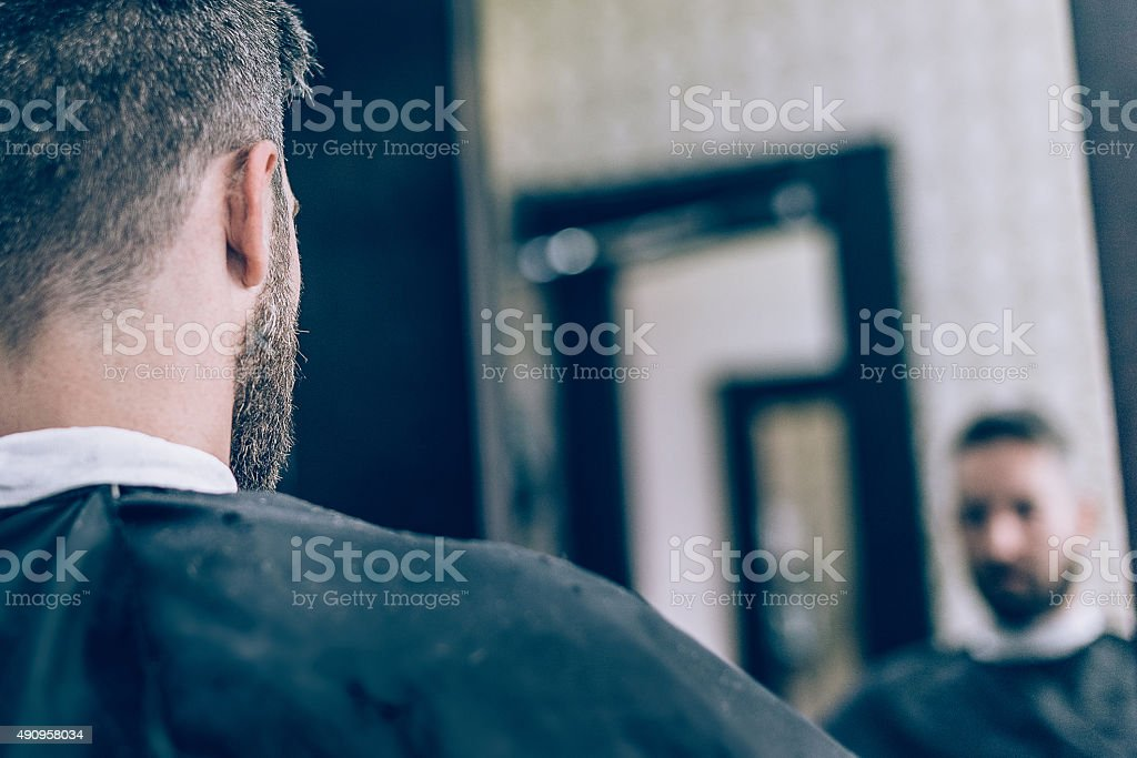 mirror view of bearded man in barber shop stock photo