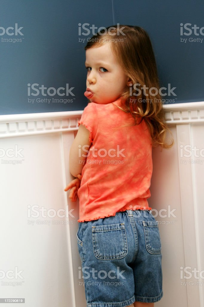 Misbehaved little girl, standing in corner, for a time out stock photo