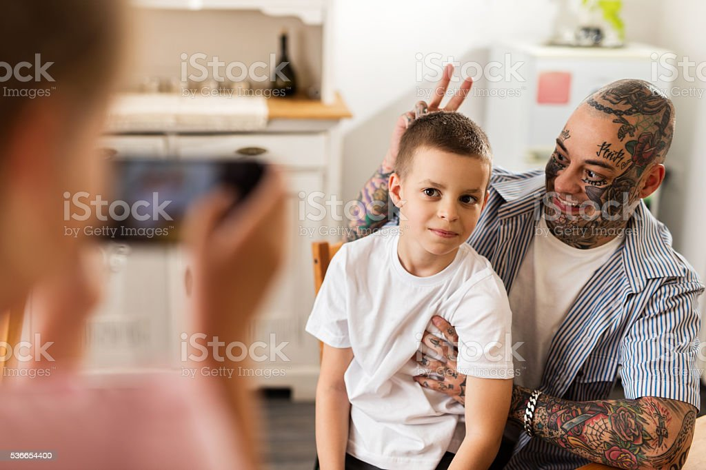 Mischief father and son being photographed with cell phone. stock photo