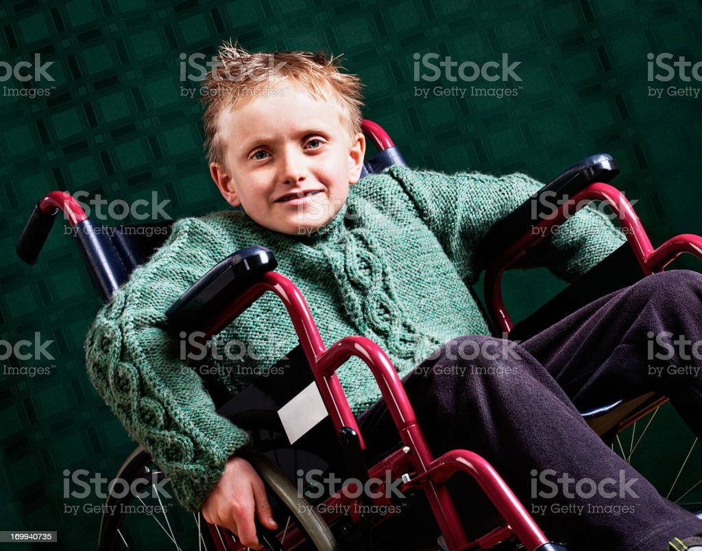 Mischievous blond boy does not let disability get him down stock photo