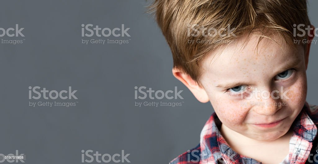 mischievous child with freckles teasing and grumbling with fun look stock photo